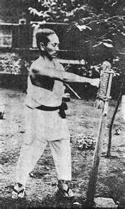 Gichin Funakoshi training with a makiwara